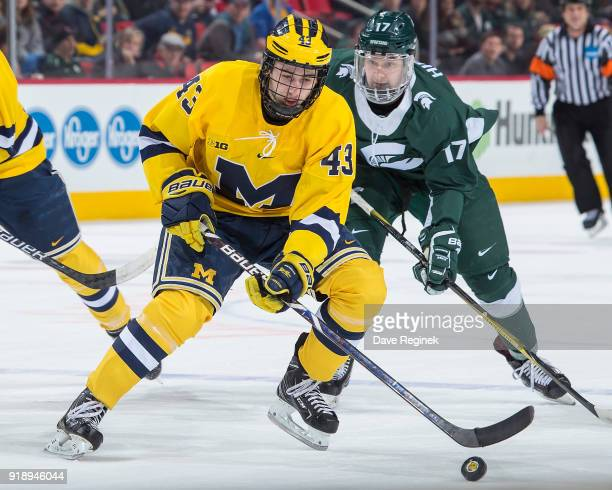 Quinn Hughes of the Michigan Wolverines controls the puck in front of Taro Hirose of the Michigan State Spartans during the Duel in the D game at...