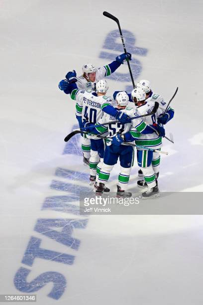 Quinn Hughes of the Vancouver Canucks is congratulated by his teammates after scoring a goal against the Minnesota Wild during the second period in...