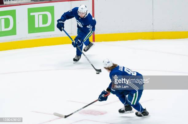 Quinn Hughes of the Vancouver Canucks passes the puck to Adam Gaudette during a drill on the first day of the Vancouver Canucks NHL Training Camp at...