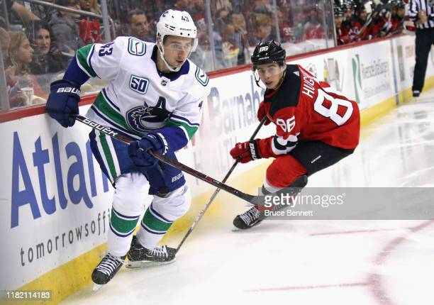 Quinn Hughes of the Vancouver Canucks skates against Jack Hughes of the New Jersey Devils during the third period at the Prudential Center on October...