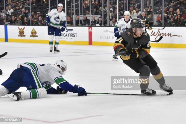 Quinn Hughes of the Vancouver Canucks trips Jonathan Marchessault of the Vegas Golden Knights with his stick during the third period at TMobile Arena...