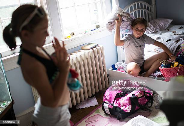 Quinn Murray hangs out at Maeve Murry's room before she goes swimming with her younger sister Coco Murray on Thursday July 24 2014 in Chevy Chase MD