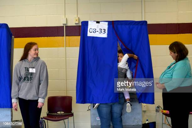 Quinn Rochester reacts as her mother casts a ballot during the midterm elections at the Milford Senior High School polling location on November 6,...