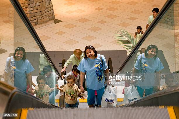 Quinn Thompson right holds a Sears shopping bag as she rides up an escalator with her grandson Andre Esquivel inside the Town Center at Aurora mall...
