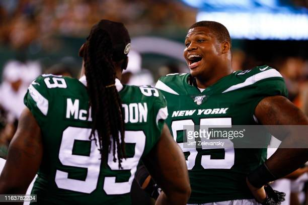 Quinnen Williams of the New York Jets talks with Steve McLendon at the bench during their preseason game against the New Orleans Saints at MetLife...