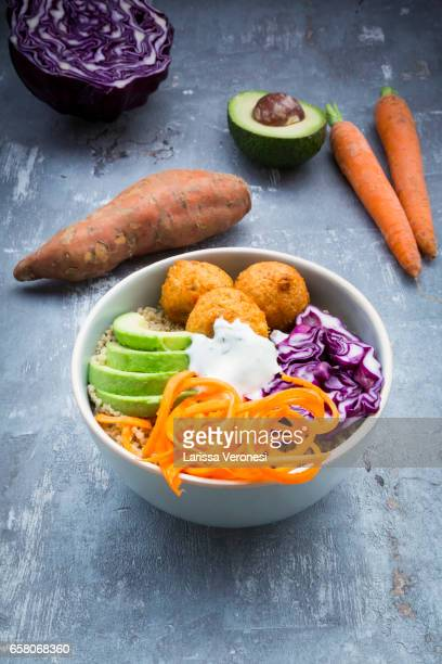 Quinoa lunch bowl with sweet potato falafel, carrots, red cabbage, avocado and yoghurt sauce