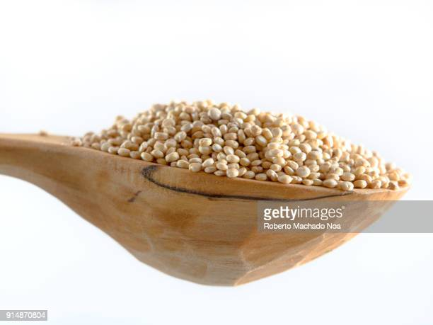 Quinoa on a wooden rustic spoon over a white background