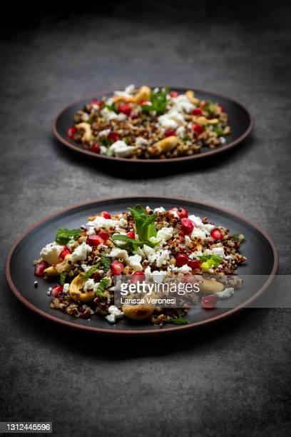quinoa salad with roasted cashews, pomegranate seeds, mint, and feta cheese - larissa veronesi stock-fotos und bilder