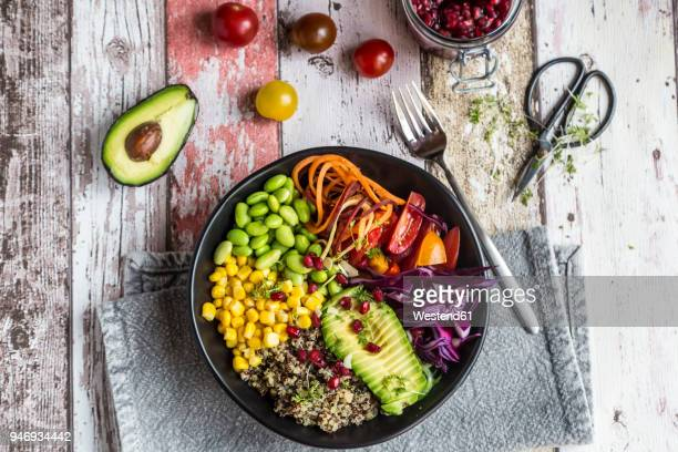 quinoa veggie bowl of avocado, edamame, tomatoes, corn, carrots, red cabbage and pomegranate seed - salad stock pictures, royalty-free photos & images