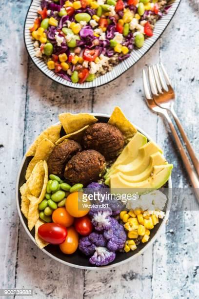 quinoa veggie bowl of avocado, edamame, tomatoes, corn, feta, nachos, cauliflower and quinoa fritters - veggie burgers stock pictures, royalty-free photos & images