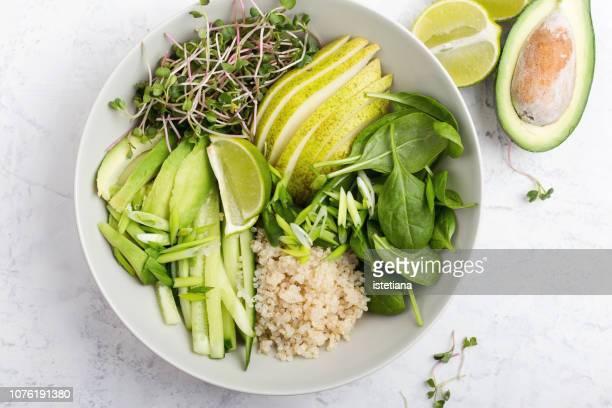 quinoa veggie bowl with green vegetables and fruits - schaal serviesgoed stockfoto's en -beelden