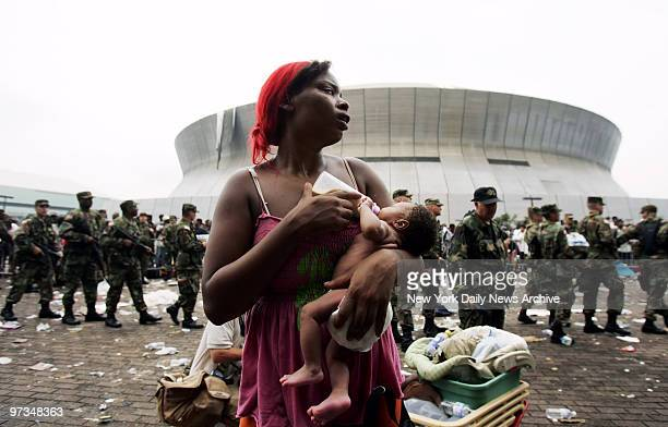 Quintella Williams feeds her 9-day-old baby girl, Akea, outside the Superdome in New Orleans, La., as she awaits evacuation from the flooded city....