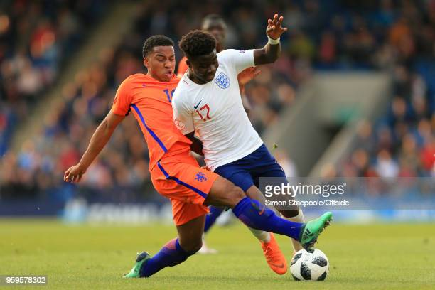 Quinten Maduro of Netherlands tackles Bukayo Saka of England during the UEFA European Under17 Championship Semi Final match between England and...