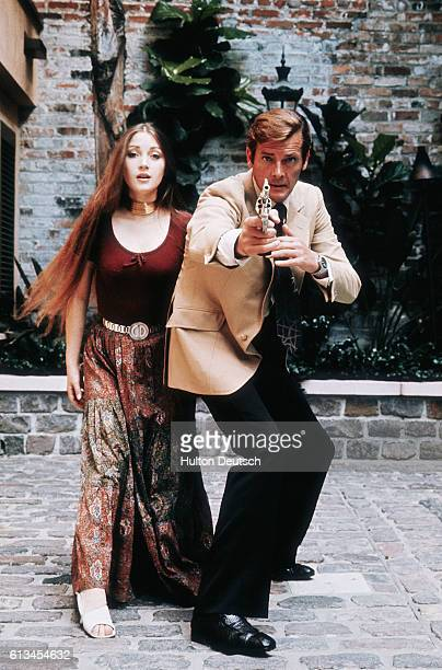 Quintessentially English actor Roger Moore and English actress Jane Seymour pose for an action shot during the filming of the 1973 James Bond film...