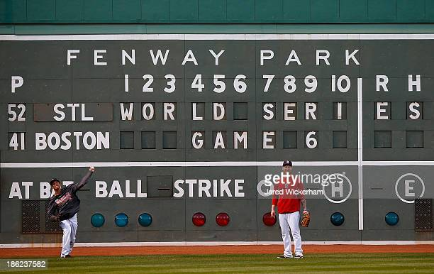 Quintin Berry of the Boston Red Sox warms up in front of the Green Monster with teammate Mike Carp of the Boston Red Sox during the team workout at...