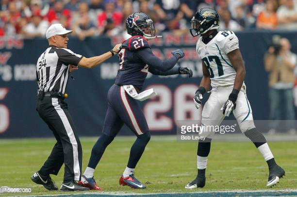 Quintin Demps of the Houston Texans is held back by referee Clete Blakeman after having words with Kevin Elliott of the Jacksonville Jaguars at...