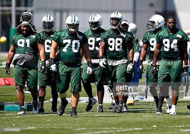 Quinton Coples of the New York Jets walks with the defensive line onto the field at an organized team activity at the New York Jets practice facility...