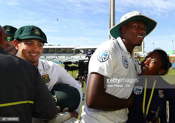 Quinton de Kock of South Africa Kagiso Rabada of South Africa and South African Team Media Manager Lerato Malekutu celebrate after day five of the...