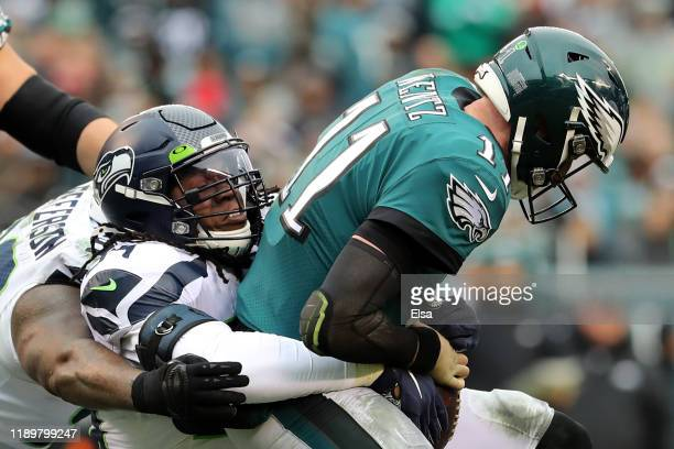 Quinton Jefferson and Ezekiel Ansah of the Seattle Seahawks sack quarterback Carson Wentz of the Philadelphia Eagles in the first half at Lincoln...