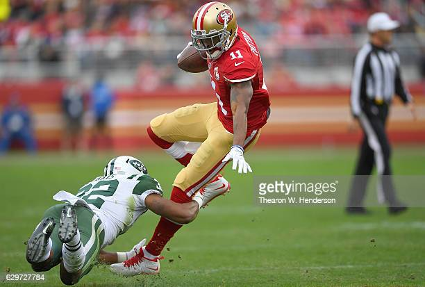 Quinton Patton of the San Francisco 49ers gets tackled by Juston Burris of the New York Jets during the first quarter of their NFL football game at...