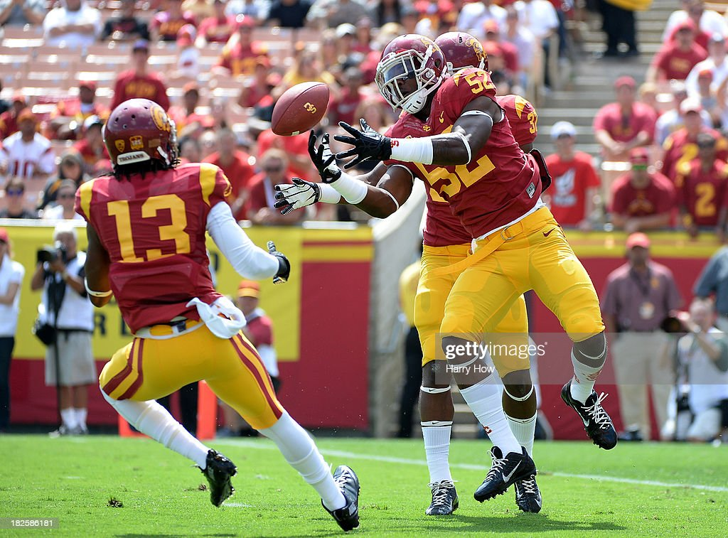Quinton Powell #52 of the USC Trojans downs a punt near the end zone in front of Kevon Seymour #13 of the USC Trojans during the game against the Utah State Aggies at the Los Angeles Memorial Coliseum on September 21, 2013 in Los Angeles, California.