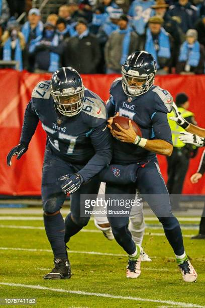 Quinton Spain of the Tennessee Titans collides with teammate Marcus Mariota against the Jacksonville Jaguars at Nissan Stadium on December 6 2018 in...