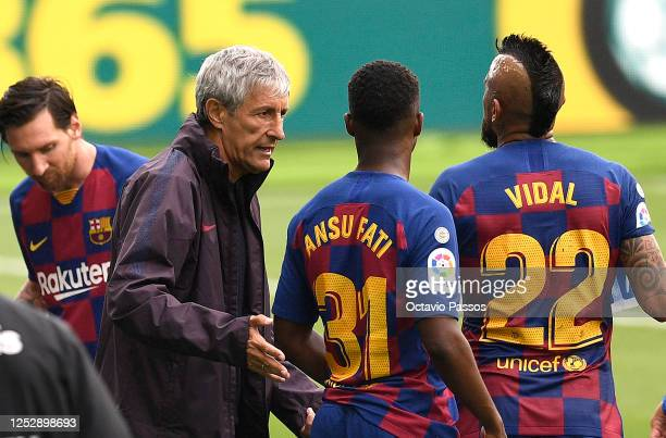 Quique Setien Head Coach of FC Barcelona speaks with Ansu Fati and Arturo Vidal of FC Barcelona at the water break during the Liga match between RC...