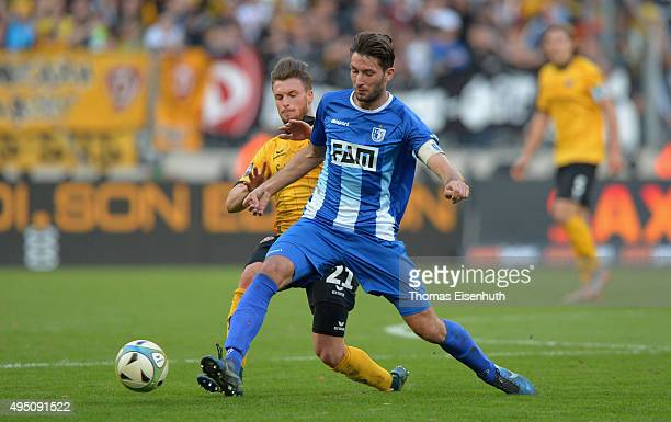 Quirin Moll of Dresden is challenged by Marius Sowislo of Magdeburg during the Third League match between SG Dynamo Dresden and 1 FC Magdeburg at...