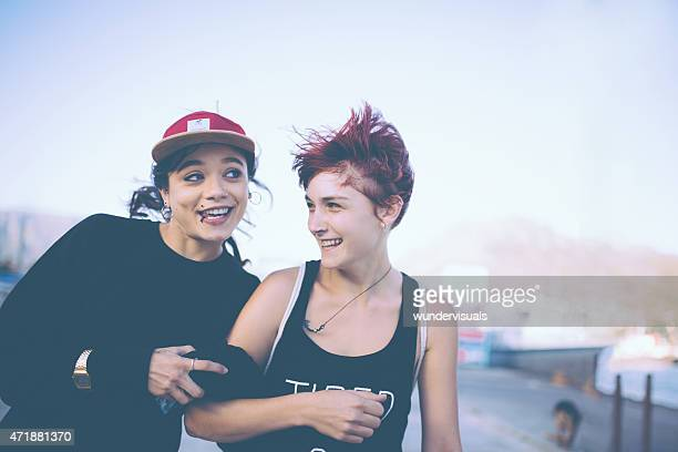 Quirky grunge girl with facial piercings smiling at her friend