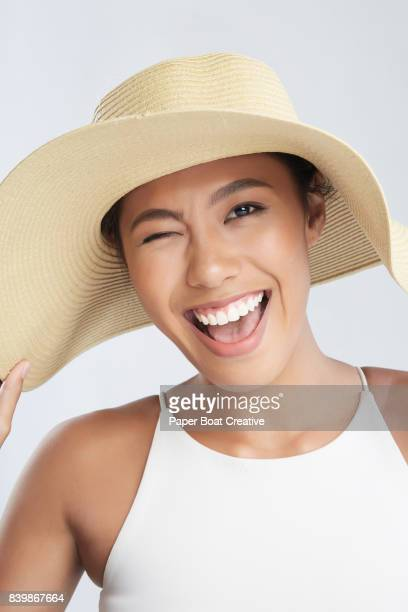 quirky looking Asian woman doing a wacky face while holding a beach hat