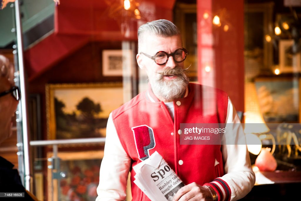 Quirky man with sports newspapers in bar and restaurant, Bournemouth, England : Stock Photo