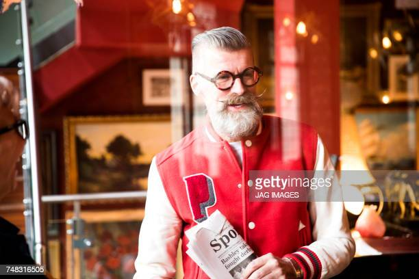Quirky man with sports newspapers in bar and restaurant, Bournemouth, England