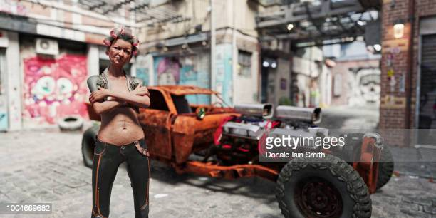 Quirky older woman in hair curlers with rusty super-car in futuristic back streets