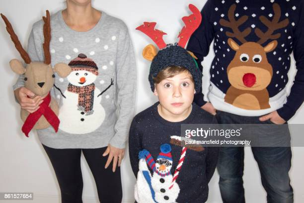 quirky portrait of family wearing christmas jumpers - renna foto e immagini stock