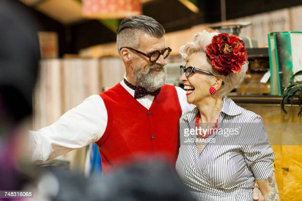 Quirky vintage couple laughing and looking at each other in antique emporium