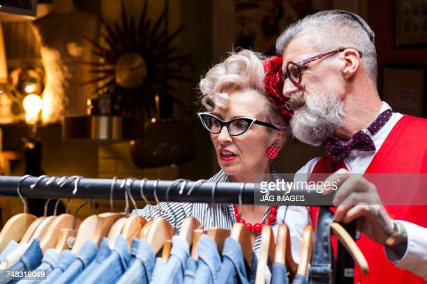 Quirky vintage couple looking at clothes rail in antiques and vintage emporium