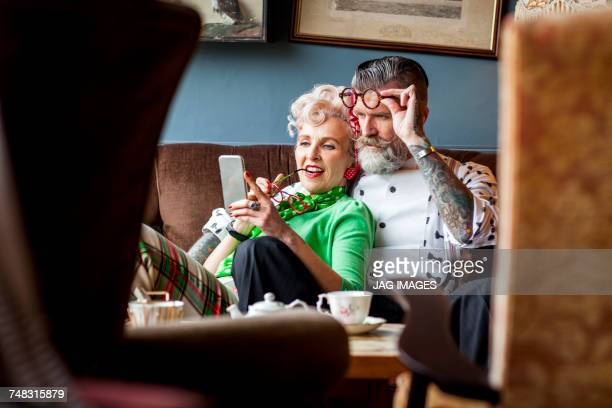 quirky vintage couple looking at smartphone in tea room - freaky couples imagens e fotografias de stock