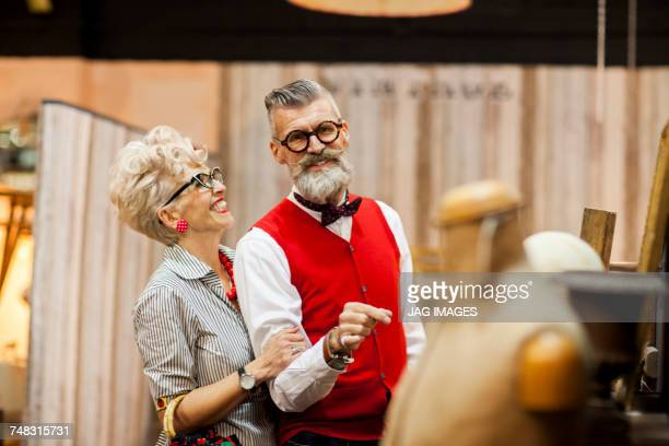 Quirky vintage couple shopping in antiques emporium