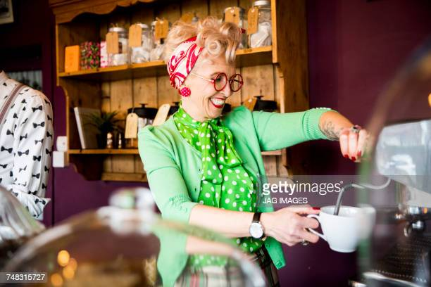 quirky vintage mature woman working behind tea room counter - serving food and drinks stock photos and pictures