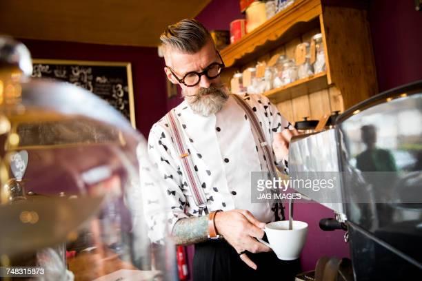 Quirky vintage senior man preparing coffee behind cafe counter
