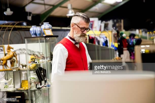 Quirky vintage senior man shopping in antiques emporium