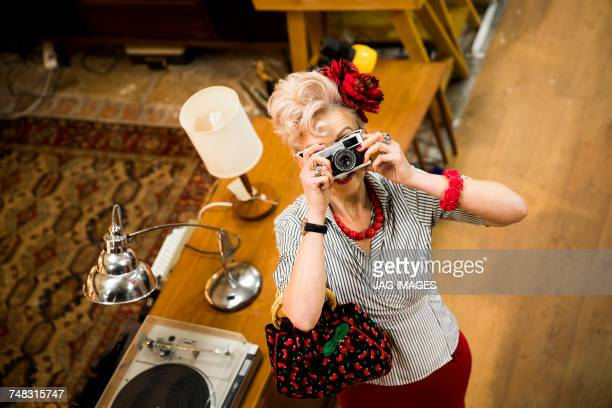 Quirky woman taking photographs on vintage camera in antiques emporium