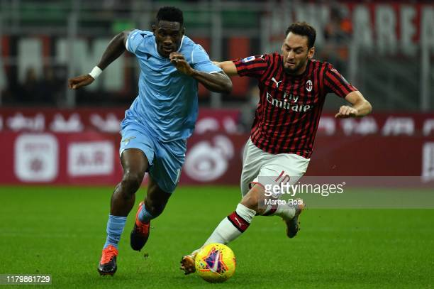 Quissanga Bastos of SS Lazio compete for the ball with Hakan Calhanoglu of AC Milan during the Serie A match between AC Milan and SS Lazio at Stadio...
