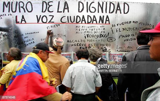 Activistas escriben consignas en un muro contra la corrupcion durante un acto para conmemorar un ano de la destitucion del ex presidente ecuatoriano...
