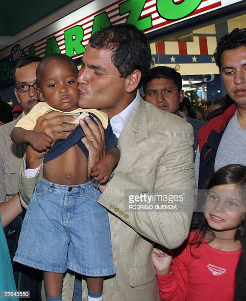 Ecuadorean presidential candidate Rafael Correa kisses a boy next to his daughter Dominique in a mall in south Quito 25 November 2006 in the eve of...