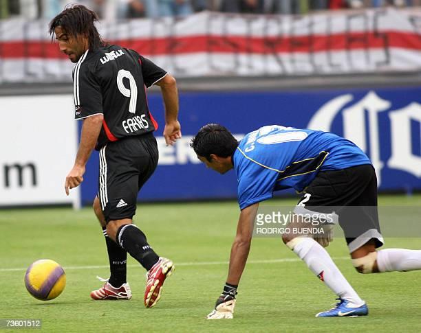 Ernesto Farias of Argentina's River Plate vies for the ball with goalkeeper Cristian Mora of Ecuador's Liga de Quito during a Libertadores Cup match...