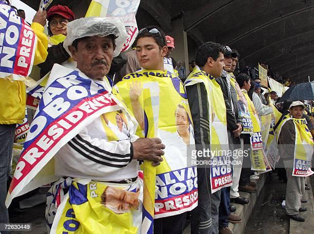 Simpatizantes del candidato presidencial Alvaro Noboa se cubren de la lluvia en el sur de Quito el 22 de noviemre de 2006 antes del inicio del acto...