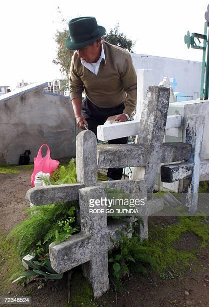 Un hombre visita la tumba comun de 5 de sus familiares fallecidos en el cementerio de Calderon a 8 km de al norte de Quito el 2 de noviembre de 2006....