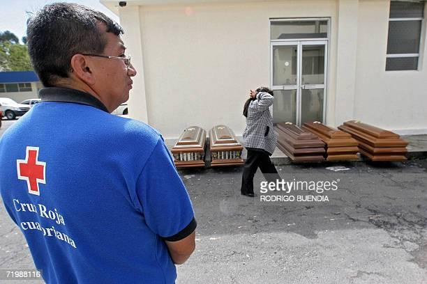Un miembro de la cruz roja observa a familiares de las victimas de un accidente de transito fuera de la morgue de Quito el 25 de setiembre de 2006 Al...