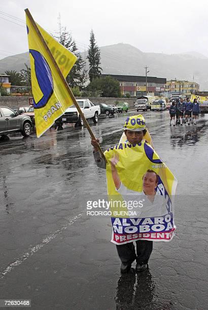 Un nino se cubre de la lluvia con afiches del candidato presidencial Alvaro Noboa en el sur de Quito el 22 de noviemre de 2006 antes del inicio del...